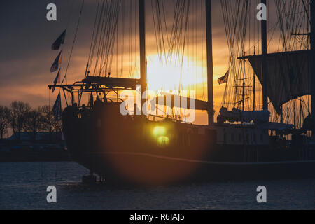 silhouette of historic sailboats on the rivers of the Netherlands. The evening falls in and in an atmospheric summer evening the boats sail over the w - Stock Photo