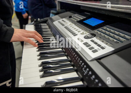 Grand synthesizer or keyboard piano with hands close up that playing the black and white keys - Stock Photo