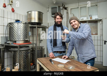 Kassel, Germany. 22nd Nov, 2018. Johannes Alt (l) and Erik Schäfer, owner of the Steckenpferd brewery, stand with a bowl of wheat malt at the brewery in the brewery. (to dpa 'Successful in the niche - Craft beer brewers assert themselves on the market' of 06.12.2018) Credit: Swen Pförtner/dpa/Alamy Live News - Stock Photo