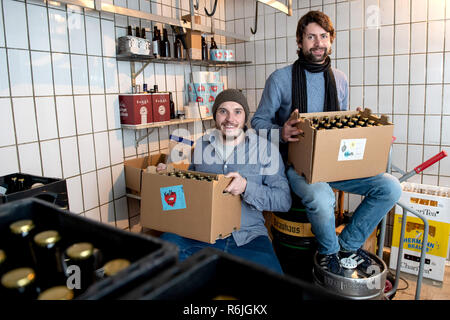 Kassel, Germany. 22nd Nov, 2018. Erik Schäfer (l) and Johannes Alt, owners of the brewery Steckenpferd, each sit with a box of Craft Beer in the lager of the brewery. (to dpa 'Successful in the niche - Craft beer brewers assert themselves on the market' of 06.12.2018) Credit: Swen Pförtner/dpa/Alamy Live News - Stock Photo