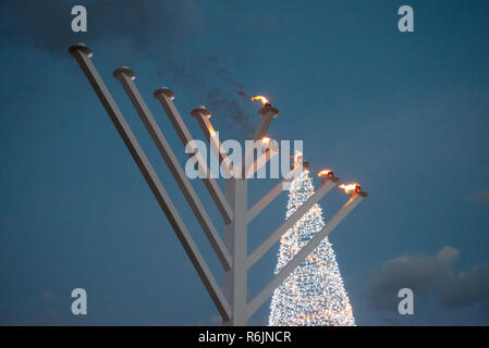 Johannesburg, South Africa, 5 December, 2018. The Jewish community lit a super-sized Menorah for Hanukkah in Sandton City, Wednesday evening. A Christmas tree made of tiny electrical lights is seen in the background. Chabad House-Johannesburg lit the 4th candle of the 7-meters-tall Menorah, symbolizing the fourth day of Hanukkah, or the Festival of Lights (saying it's the tallest Menorah in Africa). Hanukkah is celebrated 2-10 of December. Eva-Lotta Jansson/Alamy Live News - Stock Photo
