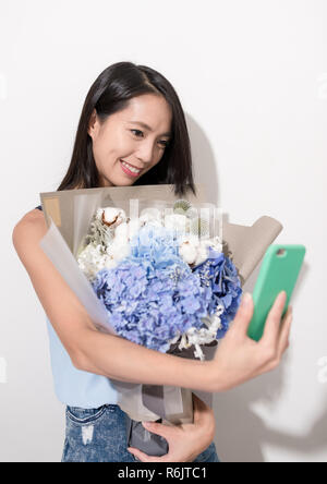 Woman holding flower to take selfie - Stock Photo