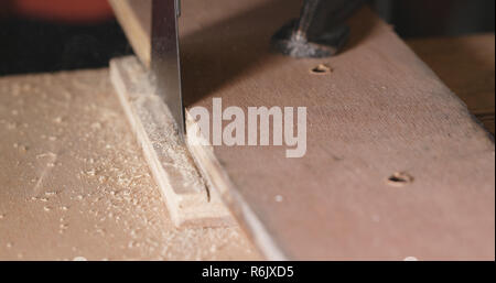 Woodworker cutting a piece of wood using a jigsaw - Stock Photo