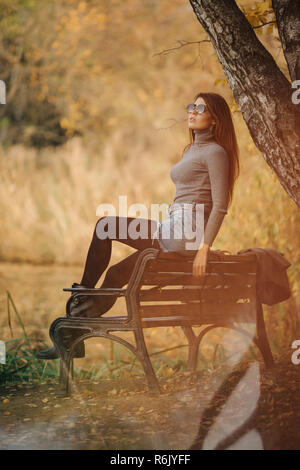 Image of woman in sunglasses sitting on bench in autumn park - Stock Photo