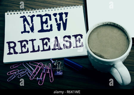 Hand writing text caption inspiration showing New Release . Business concept for Technology Software Update written on note paper on the wooden background with coffee and pen - Stock Photo