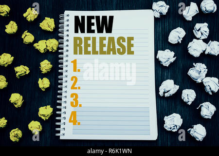 Conceptual hand writing text caption showing New Release . Business concept for Technology Software Update Written on notepad note notebook book wooden background with sticky folded yellow and white - Stock Photo