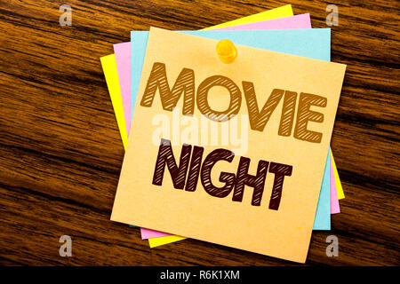 Conceptual hand writing text caption inspiration showing Movie Night. Business concept for Wathing Movies  written on sticky note paper on the wooden background. - Stock Photo