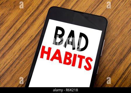 Word, writing handwriting Bad Habits. Business concept for Improvement Break Habitual Hebit Written on mobile phone cellphone, wooden background with copy space. - Stock Photo