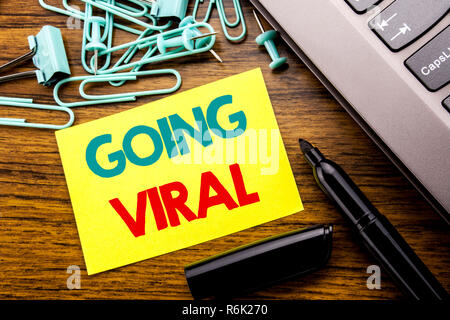 Handwriting Announcement text showing Going Viral. Business concept for Social Viral Business written on sticky note paper on the wooden background next to the laptop keyboard With marker - Stock Photo