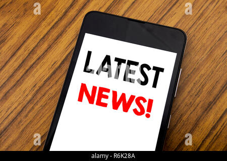 Word, writing handwriting Latest News. Business concept for Fresh Current New Story Written on mobile phone cellphone, wooden background with copy space. - Stock Photo