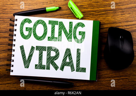 Handwriting Announcement text showing Going Viral. Business concept for Social Viral Business written on notebook book note paper on the wooden background. Green word letters. Next to mouse. - Stock Photo