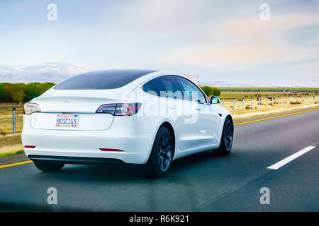 December 3, 2018 Los Angeles / CA / USA - White Tesla Model 3 driving on the freeway - Stock Photo