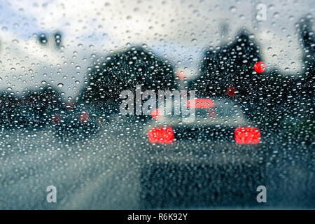 Raindrops on the windshield on a rainy day; blurred car stopped at a traffic light in the background; California - Stock Photo