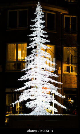 lighted up christmas tree decoration in the city streets at night - Stock Photo