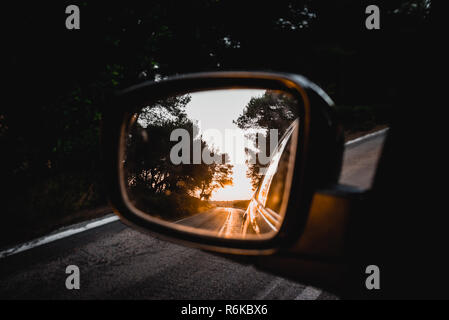 Road at sunset reflected in external car side mirror - Stock Photo