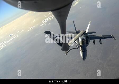 A U.S. Navy F/A-18C from the Strike Fighter Squadron VFA-37 Ragin' Bulls receives fuel in flight from a U.S. Air Force KC-135 Stratotanker over Southwest Asia May 21, 2017. Assigned to the 340th Expeditionary Air Refueling Squadron, out of Al Udeid Air Base, Qatar, the tanker from the 186th Air Refueling Wing, Mississippi Air National Guard was fitted with a drogue attached to the boom, for specialized receiver equipment on Navy and coalition aircraft. The 340th EARS maintains a 24/7 presence in the AOR, extending the missions of aircraft supporting Operation Inherent Resolve and the fight aga - Stock Photo