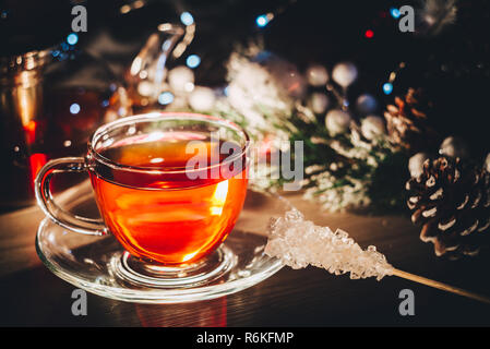Hot glass cup of black tea on table decorated with christmas tree toys