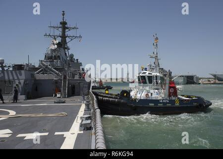 NAVAL STATION ROTA, Spain (May 24, 2017) - A tugboat guides Arleigh Burke-class guided-missile destroyer USS Carney (DDG 64) into Naval Station Rota, Spain, for a scheduled port visit May 24, 2017. Carney, forward-deployed to Rota,  is conducting its third patrol in the U.S. 6th Fleet area of operations in support of U.S. national security interests in Europe. (U.S. Navy photo by Mass Communication Specialist 3rd Class Weston Jones/Released) - Stock Photo