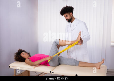 Physiotherapist Helping Patient While Stretching Her Leg