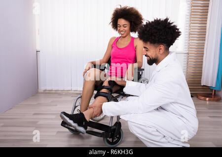 Physiotherapist Fixing Knee Braces On Woman's Leg