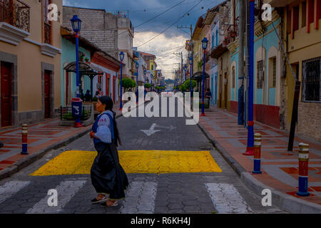 COTACACHI, ECUADOR, NOVEMBER 06, 2018: Unidentified people walking and crossing the streets in a colonial city building located in the city of Cotacac - Stock Photo
