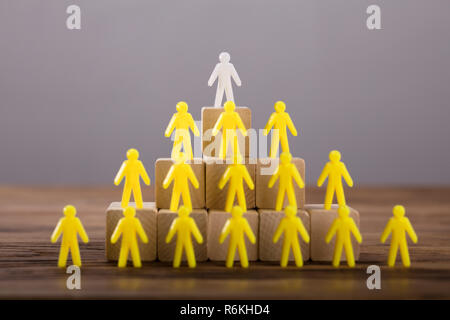 White Figure Standing On Top Of Yellow Human Figures - Stock Photo