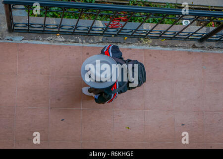 Above view of unidentified indigenous man walking in the sidewalk of Cotacachi, Ecuador. - Stock Photo