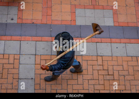 Above view of unidentified indigenous man walking in the sidewalk and holding in his back a farm machine, located in the city of Cotacachi in Ecuador. - Stock Photo