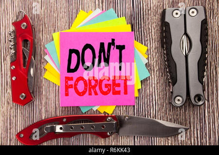 Writing text showing Do Not Forget. Business concept for Don t memory Remider Written on sticky note wooden background with pocket knife - Stock Photo