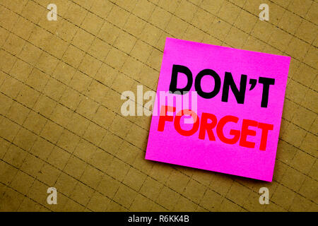 Handwritten text caption showing Do Not Forget. Business concept writing for Don t memory Remider written on sticky note paper on the yellow background. - Stock Photo