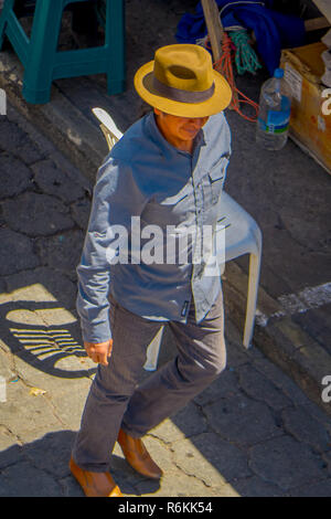 OTAVALO, ECUADOR, NOVEMBER 06, 2018 Above view of unidentified indigenous man walking in the streets of the city of Cotacachi, wearing indigenous clot - Stock Photo