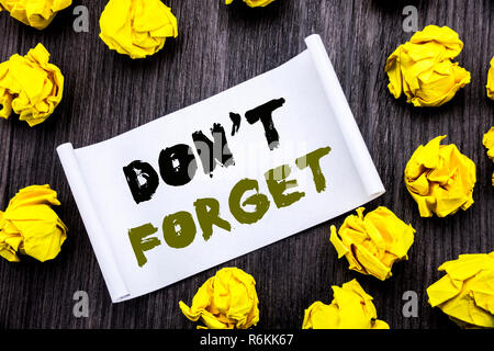 Writing text showing Do Not Forget. Business concept for Don t memory Remider Written on sticky note notepad note notebook book wooden background with yellow sticky folded. - Stock Photo
