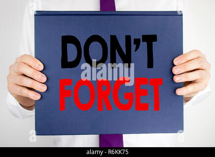 Writing text showing Do Not Forget. Business concept for Don t memory Remider written on book notebook paper holding by the man in suit blurred background. - Stock Photo