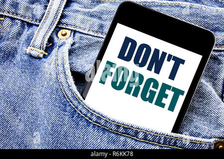 Conceptual hand writing text caption inspiration showing Do Not Forget. Business concept for Don t memory Remider Written phone mobile phone, cellphone placed in the man front jeans pocket.