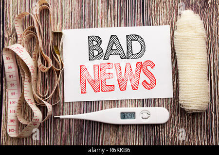 Handwritten text showing Bad News. Business fitness health concept writing for Failure Media Newspaper written sticky note empty paper background with bandage and thermometer - Stock Photo