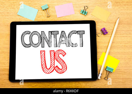 Writing text showing Contact Us. Business concept for Customer Support Written on tablet laptop, wooden background with sticky note and pen - Stock Photo