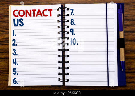 Writing text showing Contact Us. Business concept for Customer Support Written on notebook note paper, wooden background with pen and marker. - Stock Photo