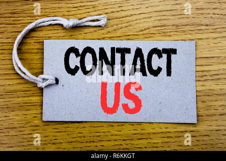 Conceptual hand writing text caption showing Contact Us. Business concept for Customer Support written on price tag paper with copy space on the wooden vintage background - Stock Photo