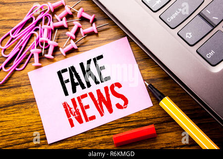 Handwritten text showing Fake News. Business concept for Hoax Journalism written on pink sticky note paper on the wooden background next to keyboard. With red pen. - Stock Photo