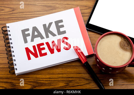 Handwriting Announcement text showing Fake News. Business concept for Hoax Journalism Written on notepad note paper on wooden background with space office view with pencil marker - Stock Photo