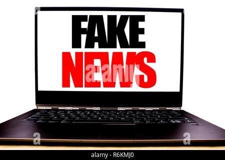 Handwritten text showing Fake News. Business concept writing for Hoax Journalism Written on monitor front screen, white background with space office view. - Stock Photo