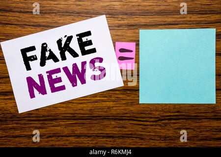 Handwriting Announcement text showing Fake News. Business concept for Hoax Journalism written on sticky note paper on wooden background. Equation mathematical sign for your space - Stock Photo