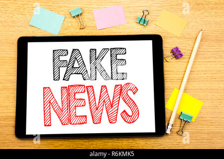 Writing text showing Fake News. Business concept for Hoax Journalism Written on tablet laptop, wooden background with sticky note and pen - Stock Photo