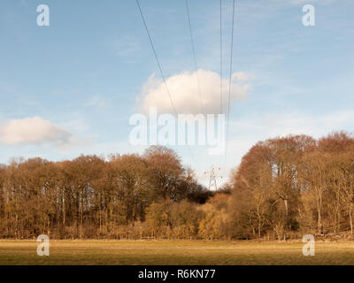 view of large electrical wire metal pylon outside in nature field wires overhead - Stock Photo