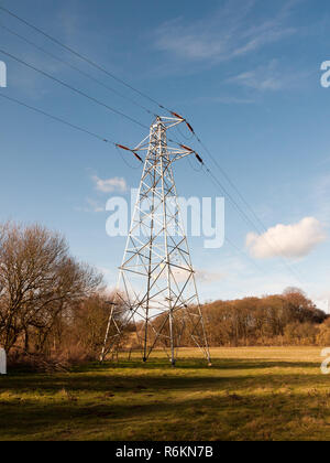 view of large electrical wire metal pylon outside in nature field - Stock Photo