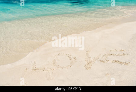 Love word written on white sand in st johns, antigua. Sea or ocean beach with turquoise water waves on sunny day. Summer vacation, holiday celebration on caribbean. Valentines day concept - Stock Photo