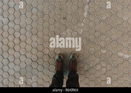 Standing on hexagonal concrete pavement tiles background, feet in sneakers from above - Stock Photo