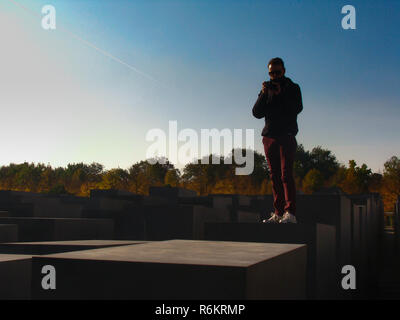 Inspired by the Jewish synagogue in Prague, this is a photo of a man standing on top of a pillar in memorial to the murdered Jews of Europe in Berlin. - Stock Photo