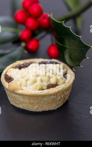 Mince pie and holly with red berries. - Stock Photo