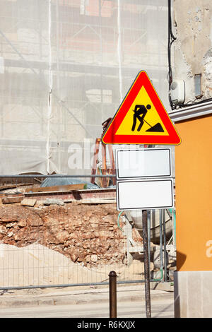 Road construction work and sign at a construction site. Warning sign under construction. Road works traffic sign in a building site - beware. - Stock Photo